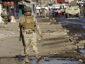 Soldado iraquiano patrulha local de atentado em Bagdá no último sábado (26) (Foto: Hadi Mizban/AP)