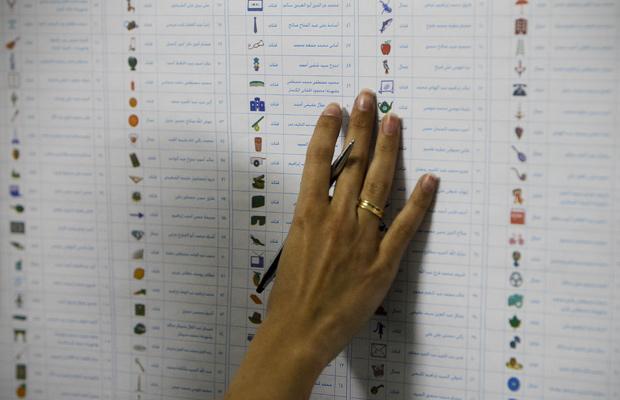 Eleitora observa cédula durante a votação nesta segunda-feira (28) no Cairo (Foto: AP)