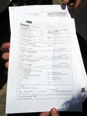 Os deputados mostram um documento do Inea com o pedido de renovação de licença da Contecom (Foto: Bernardo Tabak/G1)