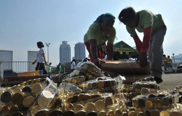 Filipinos tentam fazer fileira de 70 quilômetros usando 3.500.000 moedas. (Foto: Ted Aljibe/AFP)