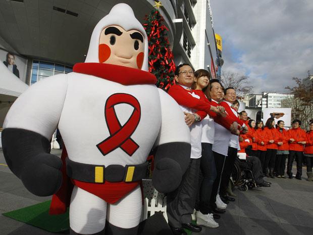 Voluntário usa fantasia de camisinha no Dia Mundial de Luta Contra a Aids, em Seul, na Coreia do Sul. Ao lado de outras pessoas, ele participa de uma campanha de conscientização sobre a doença sexualmente transmissível. (Foto: AP)