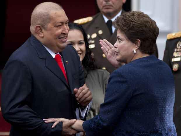 O presidente da Venezuela, Hugo Chávez, com a presidente do Brasil, Dilma Rousseff, na chegada dela ao Palácio Miraflores, em Caracas, nesta quinta-feira (1º) (Foto: AP)