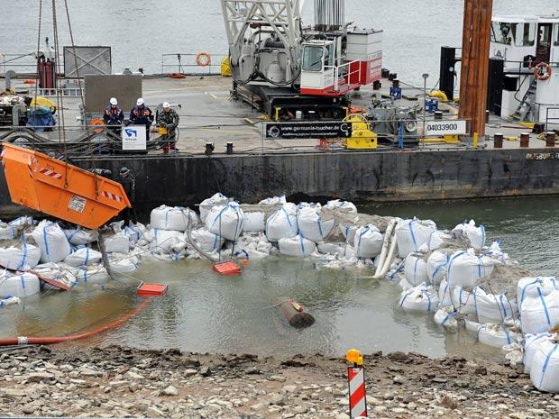 Sacos de areia foram colocados na margem do rio, na tentativa de cercar o artefato militar. (Foto: Harald Tittel/dapd/AP)