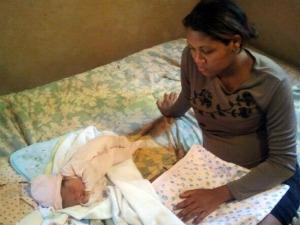 Mãe olha bebê de apenas trâs dias dormindo na cama de casa (Foto: Tawany Marry/ G1 MS)