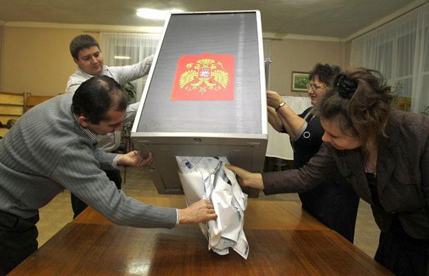 Funcionários da comissão eleitoral retiram votos de urna em Roslavl, oeste de Moscou (Foto: Sergei Grits/AP)
