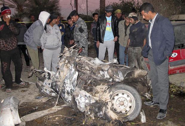 Moradores observam carro destruído por ataque a bomba em Hilla, 100 km ao sul de Bagdá (Foto: Reuters)