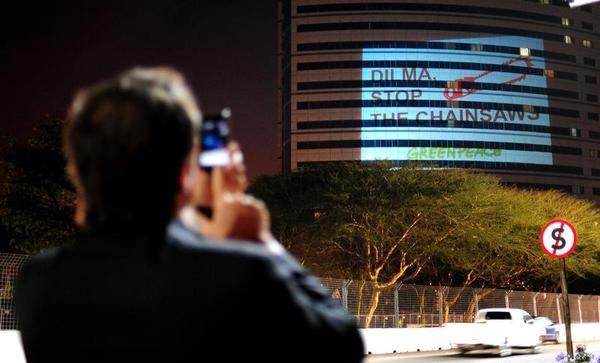 Imagem projetada em hotel de Durban, próximo ao local da COP 17, mostra imagem de motosserra e mensagem de protesto contra a votação do Código Florestal (Foto: Divulgação/Shayne Robinson/Greenpeace)