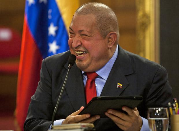 Chávez ri da foto em que aparece dando um 'selinho' em Obama ao vê-la no IPad de um jornalista durante entrevista, em Caracas (Foto: Ariana Cubillos / AP)