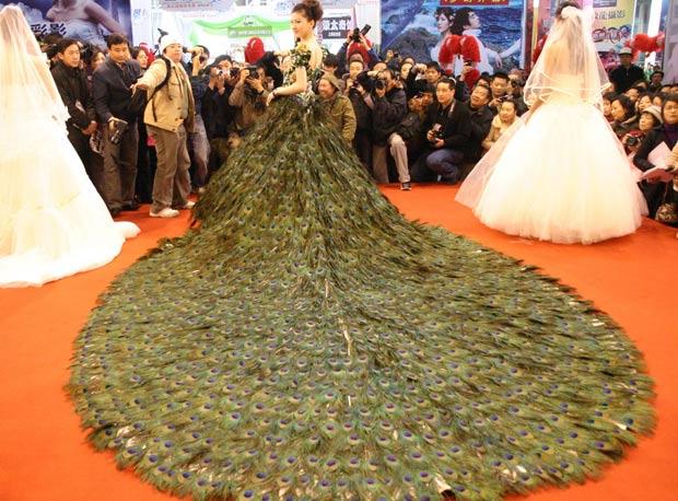 Modelo exibe vestido de casamento decorado com 2.009 penas de pavão. (Foto: AFP)