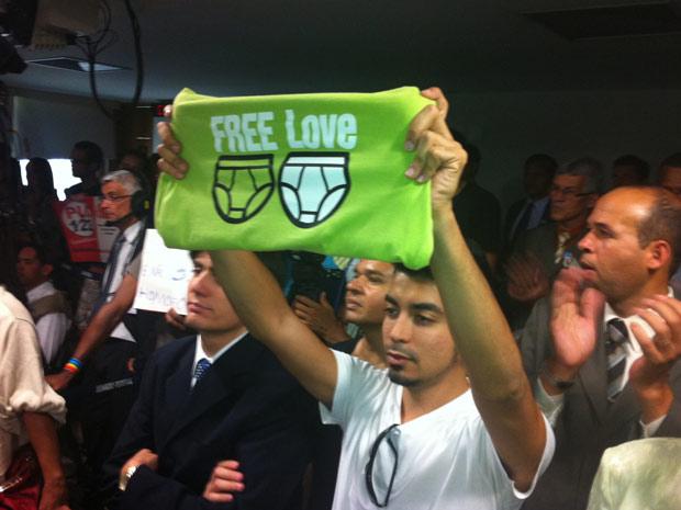 Manifestante segura cartaz durante discussão de projeto que criminaliza a homofobia (Foto: Lucas Cyrino / G1)