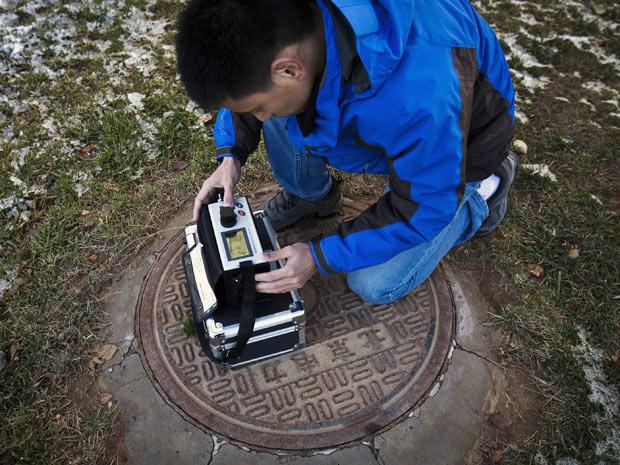 Morador de Pequim opera equipamento que monitora o nível de poluição atmosférica em conjunto residencial da cidade (Foto: Andy Wong/AP)