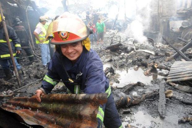 Bombeiro retira pedaço de teto de local onde avião caiu em favela de Manila, nas Filipinas, neste sábado (10) (Foto: Jay Directo / AFP)