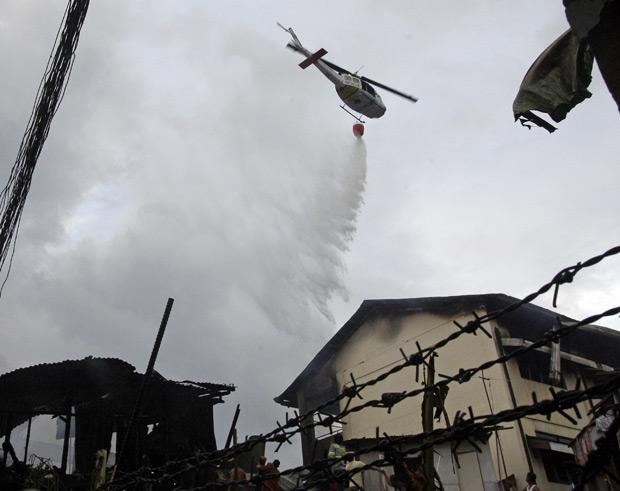 Helicóptero é utlizado para tentar conter o fogo em Paranaque, subúrbio ao sul de Manila, onde avião caiu sobre escola (Foto: Pat Roque / AP)