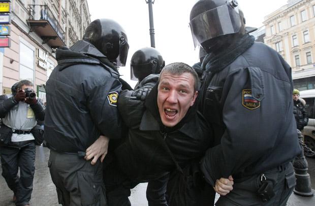 Manifestante é carregado por policiais em São Petersburgo, durante manifestação neste sábado (10) (Foto: AP)