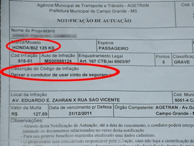 Multa recebida pelo motociclista multado por estar sem o cinto de segurança (Foto: Felipe Moura/G1 MS)