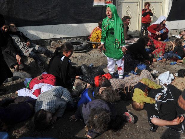 A menina, de 12 anos, grita em meio aos corpos de vítimas do ataque (Foto: Massoud Hossaini/AFP)