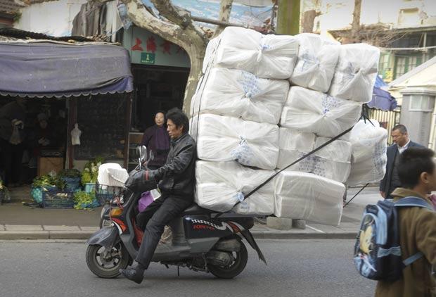 Um chinês foi fotografado andando em uma motoneta supercarregada em uma rua em Xangai. A carga era maior que o próprio veículo.  (Foto: Peter Parks/AFP)