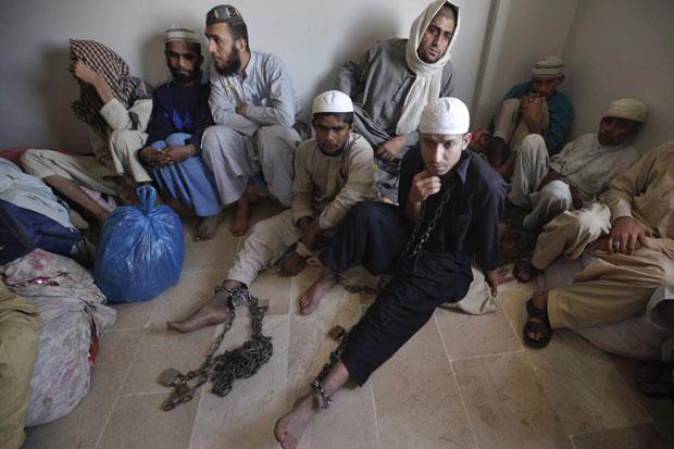 Jovens são vistos com correntes em suas pernas (Foto: Athar Hussain/Reuters)
