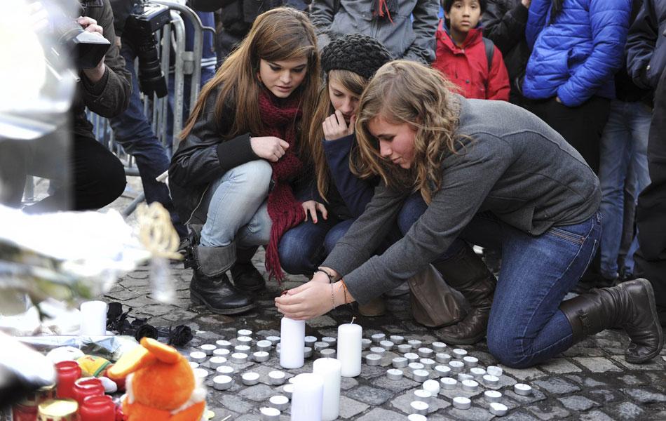 Jovens acendem velas para as vítimas do ataque