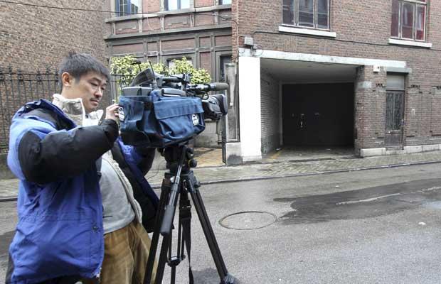 Cinegrafista em frente à casa do atirador de Liège nesta quarta-feira (14) (Foto: AP)