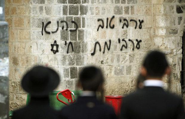 Judeus ortodoxos observam pixação em mesquita de Jerusalém Oriental. À direita, lê-se 'árabe bom é árabe morto', e à esquerda: 'Kahana está vivo' (Foto:  Ronen Zvulun/Reuters)