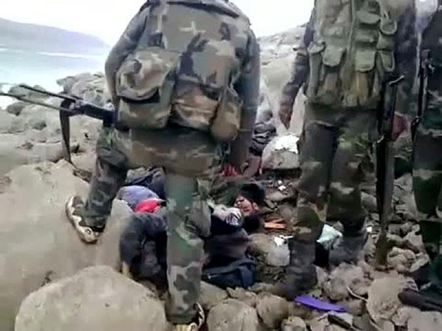 Imagem capturada de vídeo postado na internet nesta quinta (15) mostra o que seriam soldados sírios sobre corpos de militantes que teriam sido mortos pela repressão (Foto: AFP/Youtube)