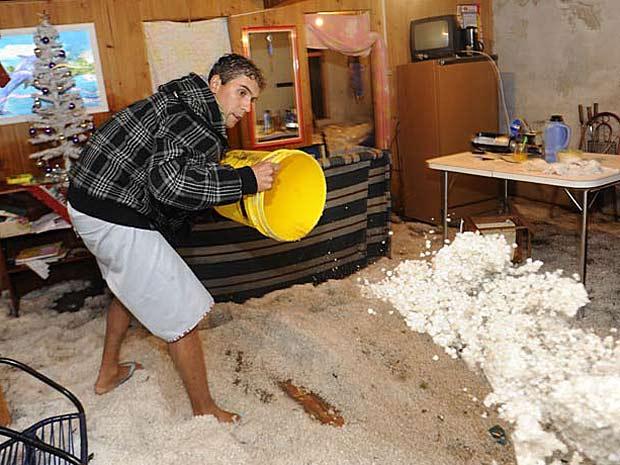 Desembargador tira o gelo que atingiu sua casa em Caxias do Sul após tempestade (Foto: Daniela Xu/Agência RBS)