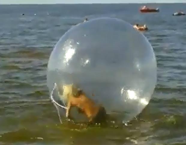 Mulher protagonizou uma cena hilária ao tentar andar dentro de bola gigante no mar. (Foto: Reprodução/YouTube)