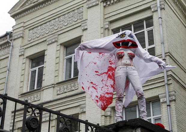 Uma ativista do grupo Femen vestiu uma fantasia e subiu no portão de um prédio governamental em Kiev, na Ucrânia, para chamar atenção ao baixo índice de mulheres atuando no governo ucraniano. (Foto: Gleb Garanich/Reuters)