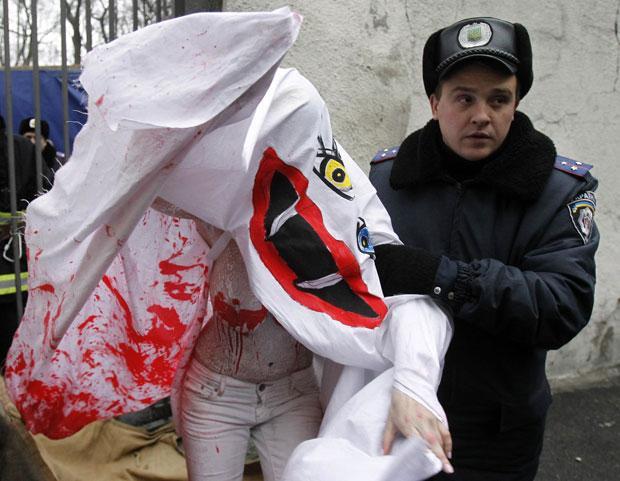 A mulher foi detida por policiais assim que desceu da grade. (Foto: Gleb Garanich/Reuters)