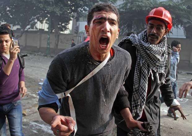 Manifestantes feridos durante confronto com militares nesta sexta-feira (16) próximo à Praça Tahrir, no centro do Cairo (Foto: AP)