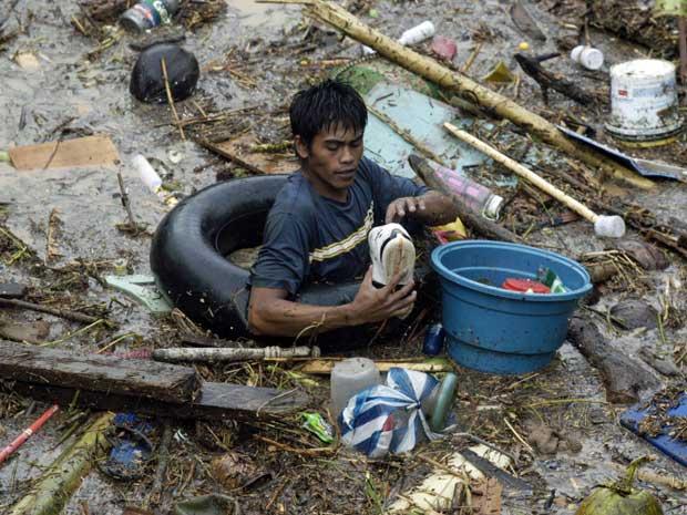 Rapaz vasculha na lama e por entre os escombros, à procura de desaparecidos. (Foto: Froilan Gallardo / AP Photo)