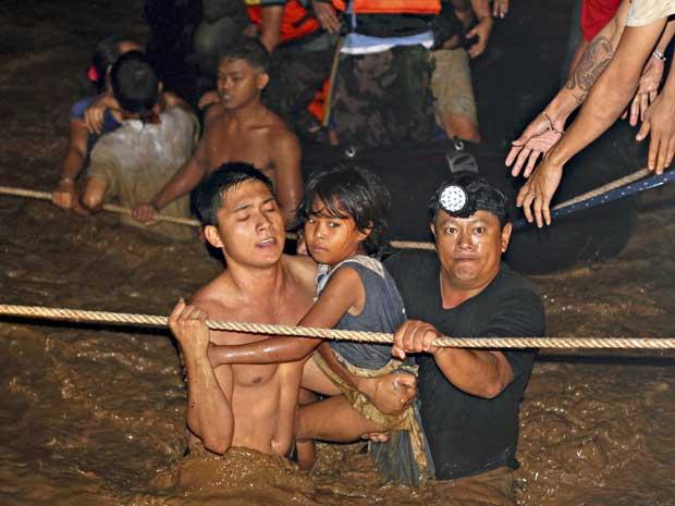 Moradores são resgatados por voluntários após inundação na cidade de Cagayan de Oro. (Foto: Erwin Mascarinas / AP Photo)