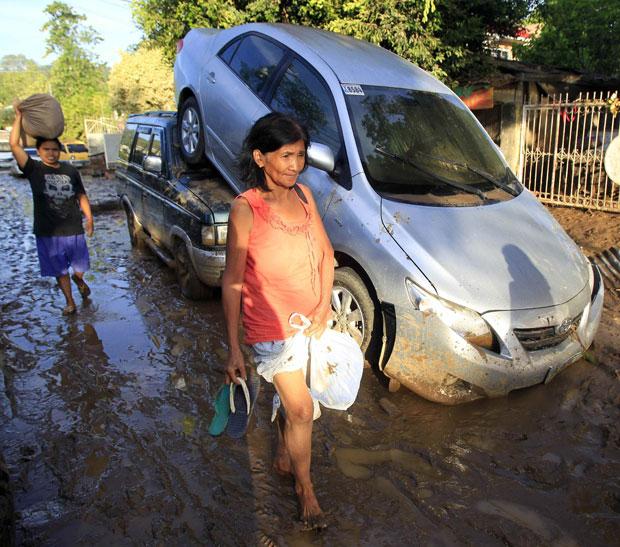 Filipinos passam em frente a carros arrastados pela enchente em Cagayan de Oro (Foto: Reuters)