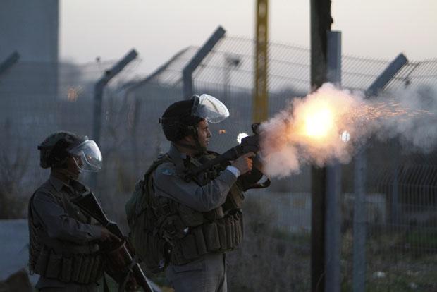 Guarda dispara granada de gás lacrimogêneo contra atiradores de pedras palestinos em frente ao presídio de Ofer, perto de Ramallah (Foto: Mohamad Torokman/Reuters)