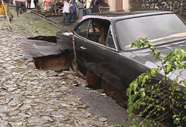 Carro é praticamente engolido por cratera provocada pela chuva, em BH (Foto: Reprodução / TV Globo)