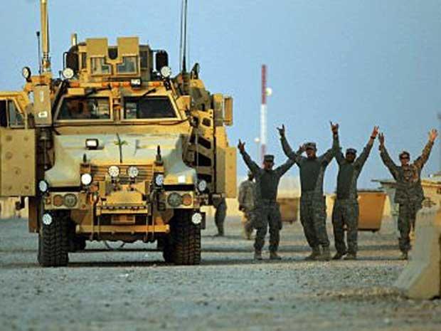 Soldados dos EUA comemoram mesmo antes de o comboio terminar viagem até o Kuwait. (Foto: Mario Tama / Pool / AFP Photo)