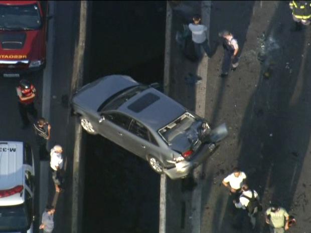 Carro fica entre pendurado entre pistas (Foto: Reprodução/TV Globo)
