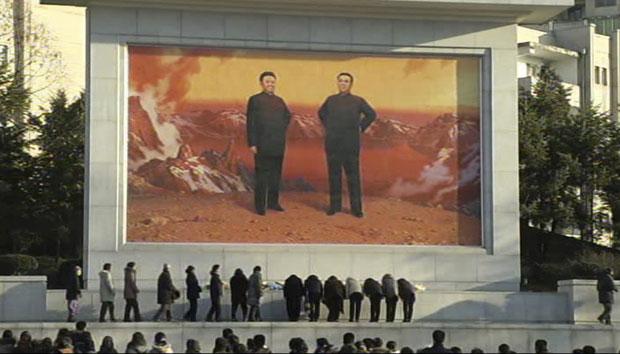 Imagem reproduzida de vídeo mostra norte-coreanos prestando homenagens a Kim Jong-il em frente a um grande mural retratando ele e o pai, Kim Sung Il, em Pyongyang (Foto: AP/APTN)