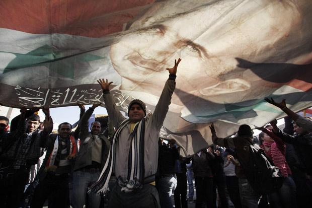 Sírios erguem bandeira com a figura do presidente Bashar al-Assad, em manifestação pró-governo nesta segunda (19), em Damasco (Foto: Muzaffar Salman / AP)