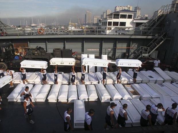 Soldados da Marinha carregam caixões de vítimas das chuvas nas Filipinas (Foto: Romeo Ranoco/Reuters)