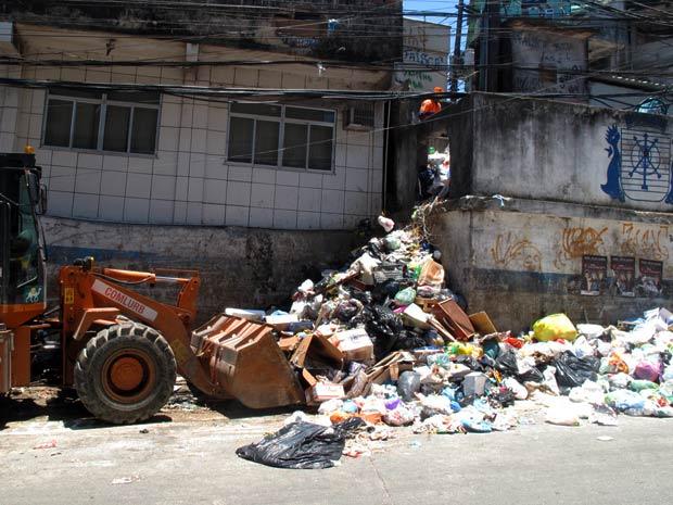 Um trator da Comlurb tenta recolher uma grande quantidade de lixo espalhada na rua (Foto: Bernardo Tabak/G1)