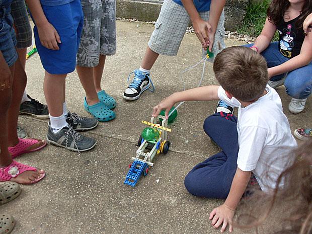 Crianças brincam com carrinho capaz de se mover com ar ou com água. (Foto: Divulgação)
