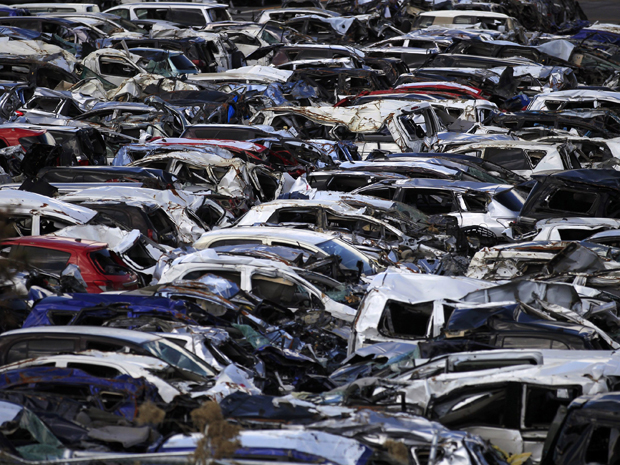 Carros novos da Toyota que foram danificados pelo tsunami de março, em estacionamento da empresa em Sendai, no Japão (Foto: Eugene Hoshiko/AP Photo)
