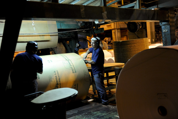 Funcionários movem rolos de papel jornal da Papel Prensa, empresa do grupo Clarín (Foto: Marcelo Genlote, Clarin / AP)