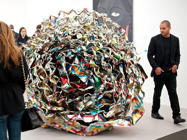 Pessoas observam escultura 'Onecaratstud', do americano John Chamberlain (Foto: Leon Neal/AFP)