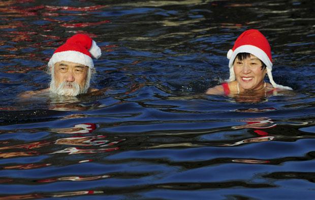 Papais e mamães noéis deram mergulho gelado em seguida, mas sem perder os gorros (Foto: Reuters/Stringer)