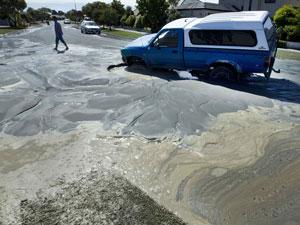 Carro é parcialmente engolido por um buraco que se formou após tremores (Foto: Simon Baker/Reuters)