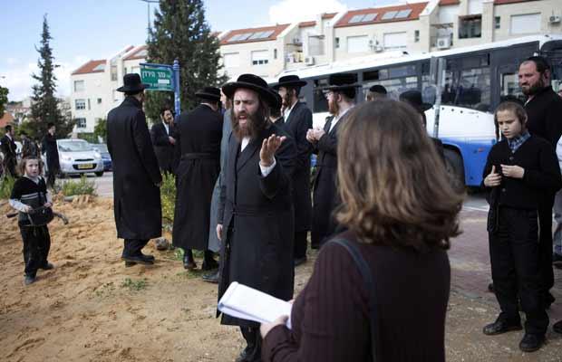 Judeu ultra-ortodoxo discute com jornalista nesta sexta-feira (26) em Beit Shemesh (Foto: AFP)