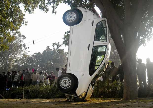 Carro fica preso em árvore após colisão em alta velocidade nesta segunda-feira (26) na cidade indiana de Gurgaon. O motorista escapou com ferimentos leves, segundo a imprensa local (Foto: AP)